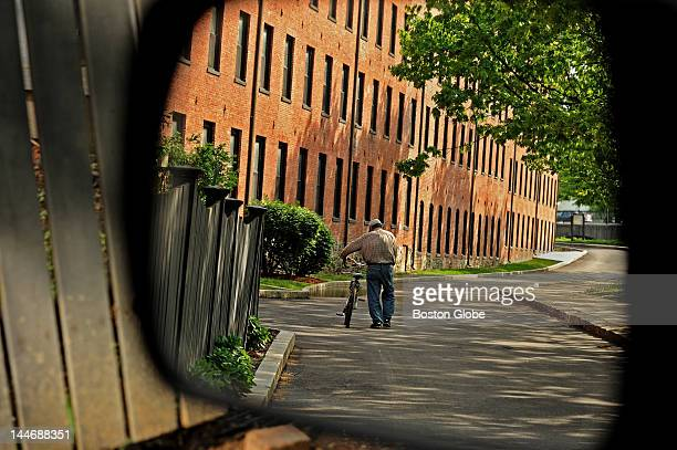 As seen through a rearview mirror a man walks his bicycle as he strolls next to the Charles River in Waltham by the Francis Cabot Lower Mills...