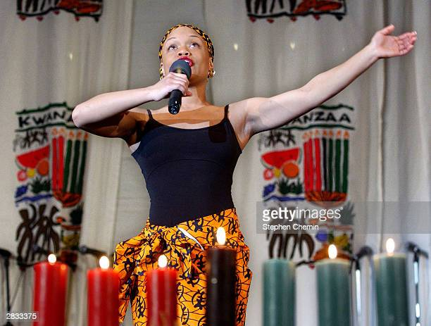 As seven Kwanzaa candles burn Malaiyka Reid of Brooklyn New York reads poem titled 'Ego Trippin' during a Kwanzaa celebration December 27 2003 at The...
