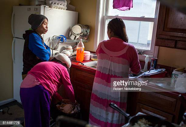 As she washes dishes in her kitchen Hema Gurung talks with her brotherinlaw Dambar Gurung and motherinlaw Man Maya Gurung Burlington Vermont December...