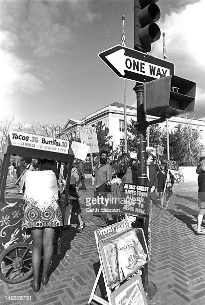 As student demonstrators walk in a picket line at the Sather Gate entrance to the University of California a small food cart serves tacos and...
