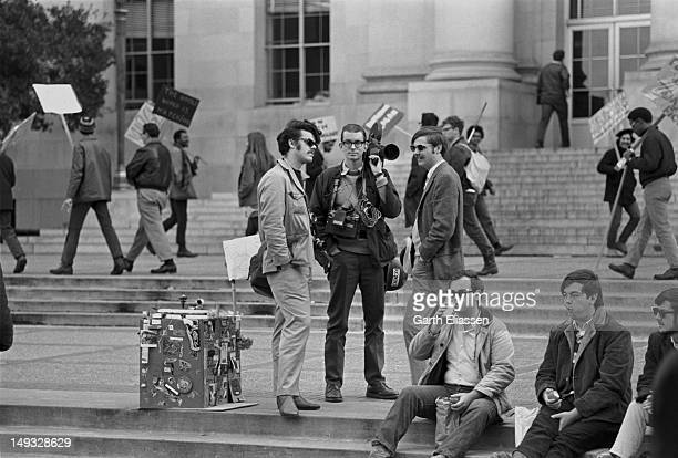 As students demontrate in the background, photographer Nacio Jan Brown and two unidentified journalists from San Francisco Public Radio station KQED...