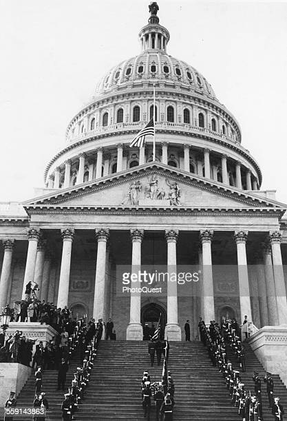 As television cameras watch, an honor guard and mourners stand at attention as member of the Kennedy family follow the coffin of assassinated US...