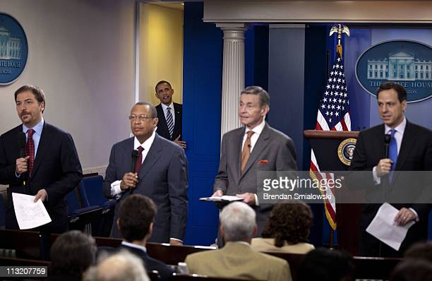 As television reporters talk President Barack Obama arrives to speak to the press in the Briefing Room of the White House April 27 2011 in Washington...