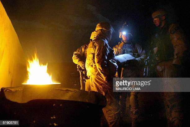 As temperature reaches zero degree Celsius US soldiers from the 1st Battalion 24th Infantry Regiment make plans next to a trash fire in Mosul 370 km...