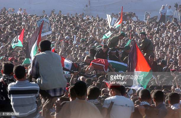 As the casket of the late Palestinian leader Yasser Arafat is moved from the Egyptian helicopter to the grave site inside the Mukata compound in...