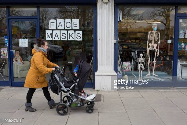 As the Coronovirus pandemic takes hold across the UK with 53 cases now reported by health authorities a mother and child walks past the window of a...