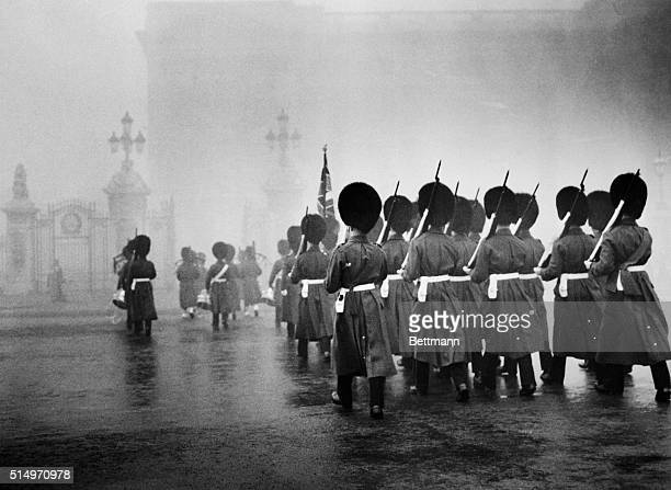 As the dense blanket of fog hides most of London from view Scots Guards march towards Buckingham Palace to take up sentry duty With the capital city...