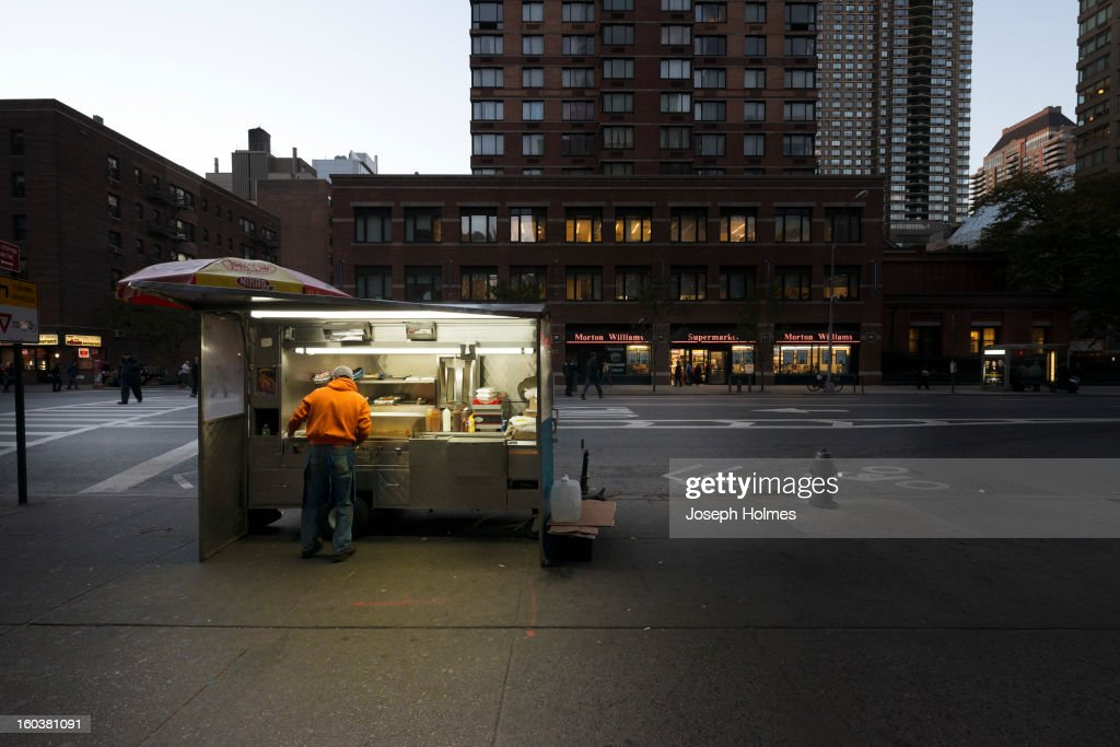 CONTENT] As the evening falls, a vendor cooks in his mobile food stand in Manhattan's Hell's Kitchen neighborhood.