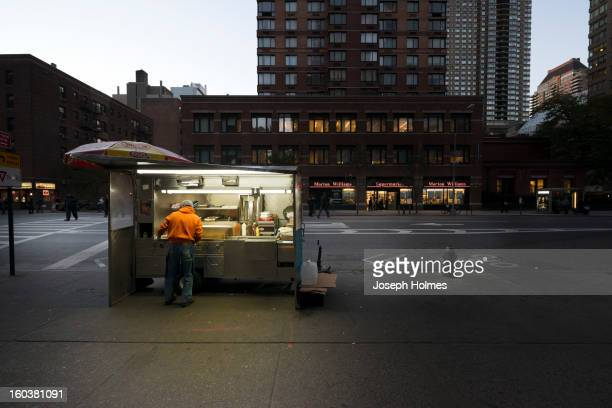 As the evening falls, a vendor cooks in his mobile food stand in Manhattan's Hell's Kitchen neighborhood.