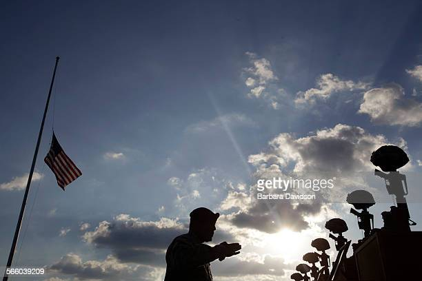 As the flag flies at half mast a soldier prepares to salute the memorial honoring the fallen after President Obama and first lady Michelle Obama...