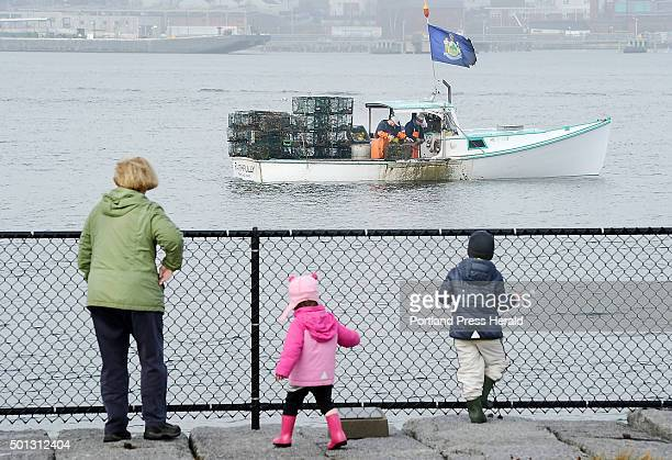 As the fog lifts Kathy O'Donnell of South Portland enjoys a close look of lobstermen pulling traps with her grandchildren Emma and Collin O'Donnell...