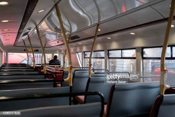 As the government announces the move from Tier 2 to Tier 3 before Christmas, a lone bus pasenger travels on the top deck through Piccadilly during...
