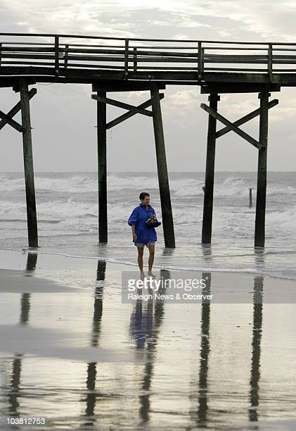 As the morning sun breaks through the clouds Nancy Brady walks by the Oceanana Fishing Pier on Atlantic Beach North Carolina Friday September 3 2010...