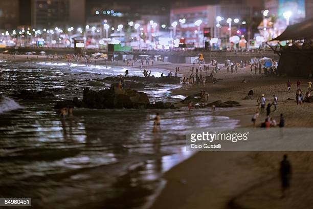 As the multitude crosses the Barra Ondina track during the late night other carnival revellers walk in the beach on February 21 in Salvador Brazil