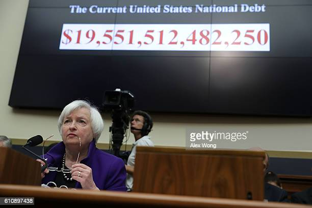 As the number of the current US national debt is seen on a screen Federal Reserve Board Chair Janet Yellen testifies during a hearing before the...