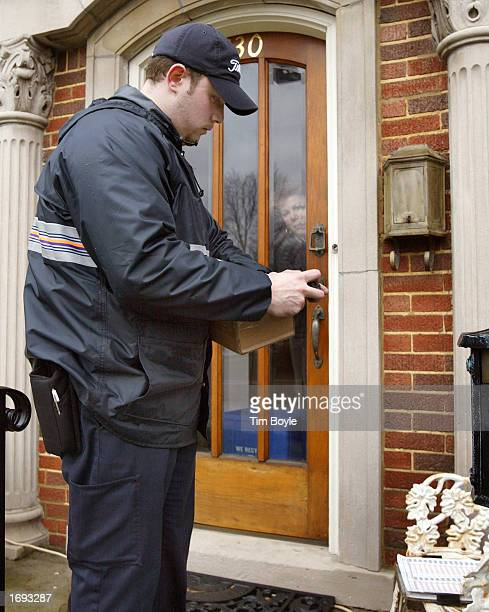As the package recipient looks out through her door, FedEx delivery person Nate Giacalone prepares to deliver a package December 18, 2002 along his...