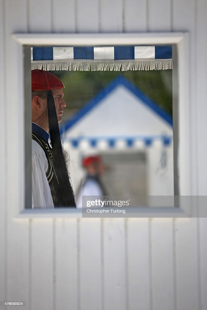 As the people of Greece vote in the referendum an 'Evzones' presidential guard stands in his sentry box outside the Greek parliament on July 5, 2015 in Athens, Greece. The people of Greece are going to the polls to decide if the country should accept the terms and conditions of a bailout with its creditors. Greek Prime Minister Alexis Tsipras is urging people to vote 'a proud no' to European creditors' proposals, and 'live with dignity in Europe'. 'Yes' campaigners believe that a no vote would mean financial ruin for Greece and the loss of the Euro currency.