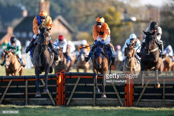 As the runners clear the last in The AJA Amateur Riders' Handicap Hurdle Mr M Galligan riding Flashjack and Miss Issabel Williams riding Virginia...
