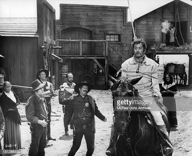 As the sheriff prepares to whip the horse from under Eli Wallach Clint Eastwood fires from a nearby stable to cut Eli's noose in a scene from the...