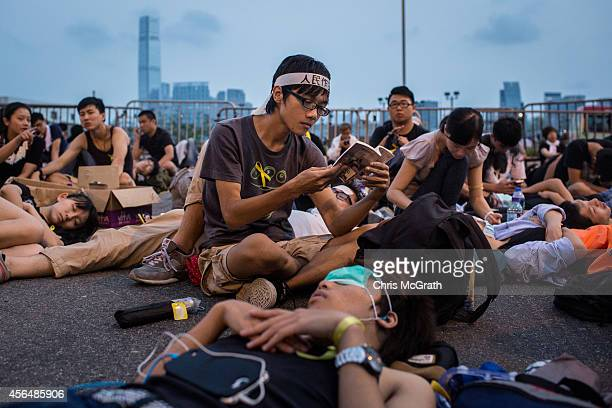 As the sun comes up a protester reads a book at a sit in blocking the entrance to the Chief Executive's Office on October 2 2014 in Hong Kong Hong...