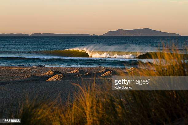 As the sun rises a wave breaks just off the sand in Oxnard, California.  The sun is also lighting up Anacapa Island, which is part of Channel Islands National Park.