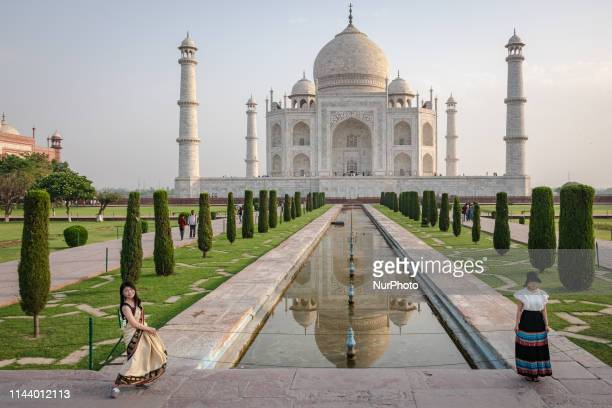 As the sun rises on 15 May 2019, Asian tourists pose for photos in front of the Taj Mahal, one of the Seven Wonders of the World. The Taj Mahal is a...