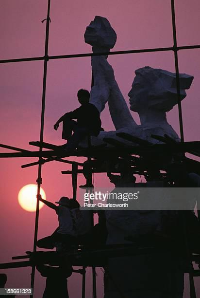 "As the sun rises, pro-democracy student demonstrators erect the ""Goddess of Democracy"" in Tiananmen Square.."
