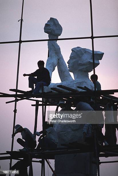 As the sun rises prodemocracy student demonstrators erect the 'Goddess of Democracy' in Tiananmen Square Art students made the polystyrene and...