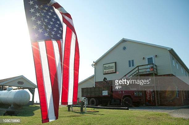 As the sun rises the US flag hangs on the side of the road at the AE Phillips Inc plant in Fishing Creek MD July 22 2010 The plant is the original AE...