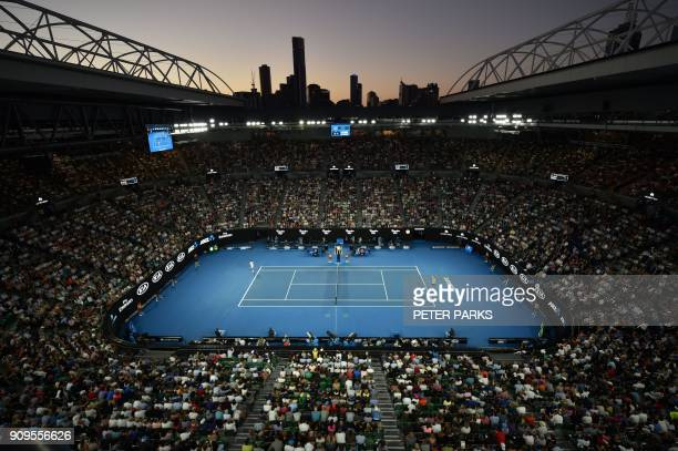 TOPSHOT As the sun sets behind the city skyline Switzerland's Roger Federer plays against Czech Republic's Tomas Berdych during their men's singles...