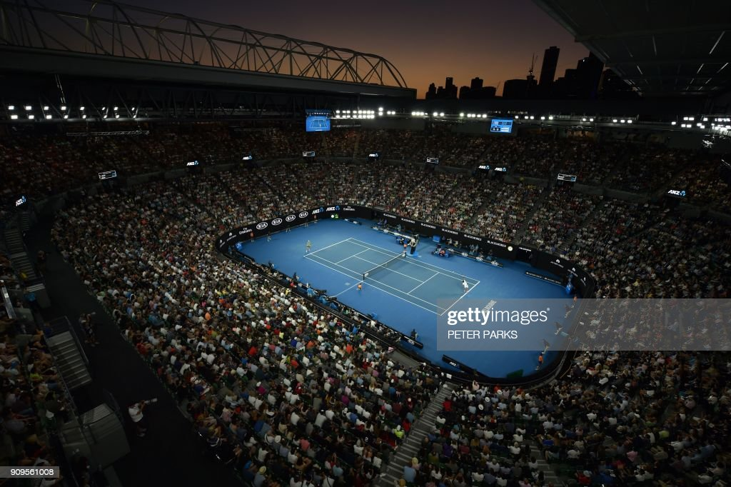 As the sun sets behind the city skyline, Switzerland's Roger Federer (R) plays against Czech Republic's Tomas Berdych during their men's singles quarter-finals match on day 10 of the Australian Open tennis tournament in Melbourne on January 24, 2018. /