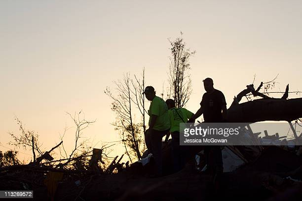 As the sun sets, firefighters help in search and rescue efforts in the Rosedale community on April 28, 2011 in Tuscaloosa, Alabama. The tornado that...