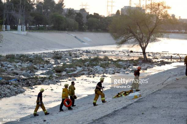 As the sun sets Los Angeles Firefighters walk up the steep embankment adjacent to the Los Angeles river next to the five freeway in Griffith Park in...