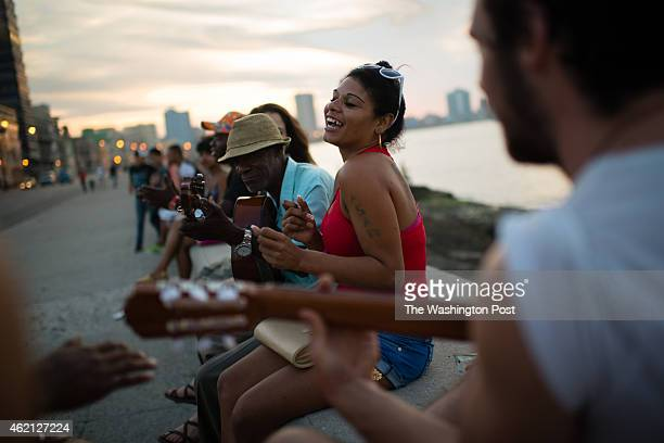 As the sun sets on the Malecon in Havana on Friday January 23 Surenis Angulo de la Paz center dances as group of locals play music around her Behind...