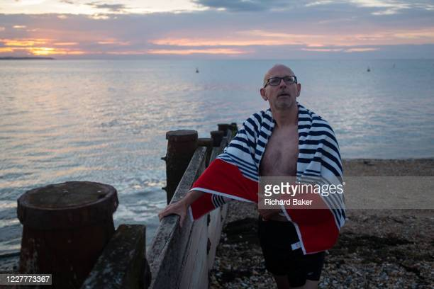 As the sun sets over fading daylight and calm waters of the Thames Estuary, a wild sea swimmer dries himself with a beach towel after his regular...