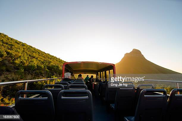 As the sun sets over the cape, an open-top bus winds its way down Cape Town's most distinctive mountain, 2012