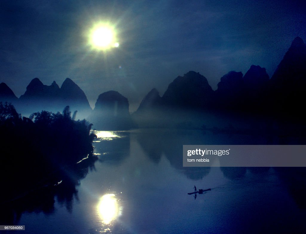 As the sun sets over the karsts along the Li River, a man poles a raft through the mist, Yangshuo, Guangxi province, China, April 1980.