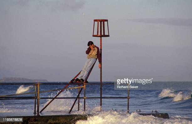 As the surf splashes around him a young man stands on iron railings and wipes his face on 20th October 1990 in Bournemouth England
