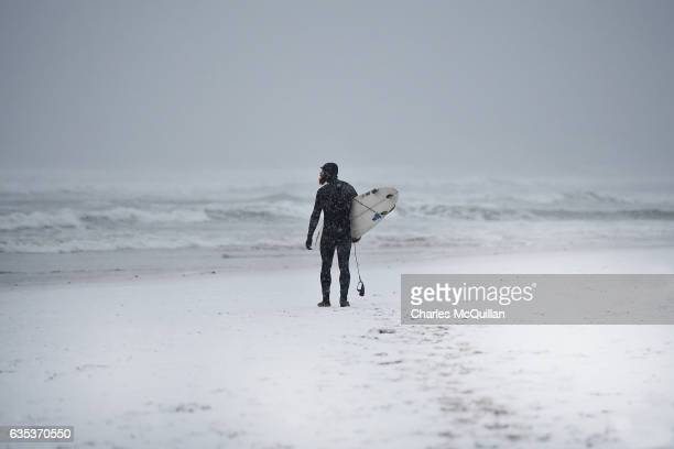As the temperature drops and snow begins to fall surfer Al Mennie makes his way towards the north Atlantic on January 12 2017 in Portrush Northern...