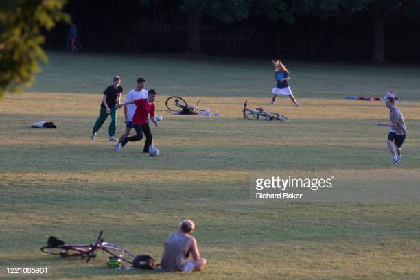 As the UK Coronavirus pandemic lockdown continues but with restrictions easing, south Londoners enjoy the last weekend sunshine by playing football...