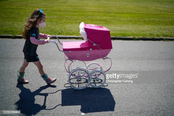 As the UK government ease lockdown restrictions and wearing masks becomes the 'new normal' a young girl walks her toy dolls in her perambulator in...