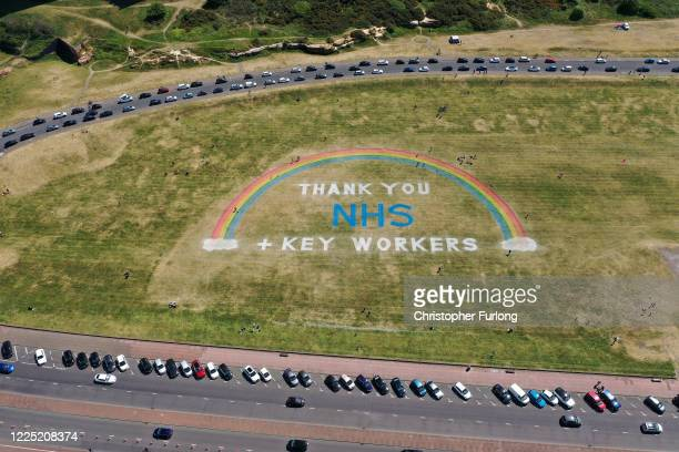 As the UK government ease lockdown restrictions people exercise and view a giant rainbow mural created by Wirral Council to thank NHS and key workers...