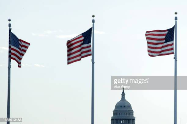 As the US Capitol is seen in the background US flags fly near the Washington Monument on Flag Day June 14 2019 in Washington DC The nation observes...