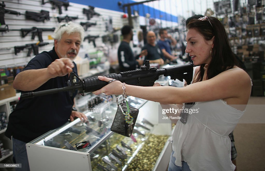 As the U.S. Senate takes up gun legislation in Washington, DC , Dr. Gary Lampert (L), a co-owner of the National Armory gun store, helps Cristiana Verro consider fire arms on April 11, 2013 in Pompano Beach, Florida. The Senate voted 68-31 to begin debate on a bill that would significantly expand background checks for gun sales.
