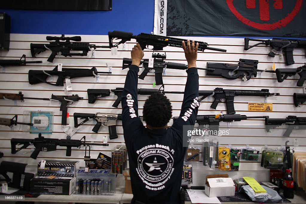 As the U.S. Senate takes up gun legislation in Washington, DC , Mike Acevedo puts a weapon on display at the National Armory gun store on April 11, 2013 in Pompano Beach, Florida. The Senate voted 68-31 to begin debate on a bill that would significantly expand background checks for gun sales.
