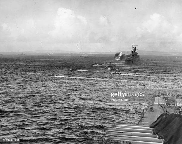 As the USS Indianapolis fires loaded landing craft move toward shore on DDay Saipan in the Marinana Islands June 15 1944