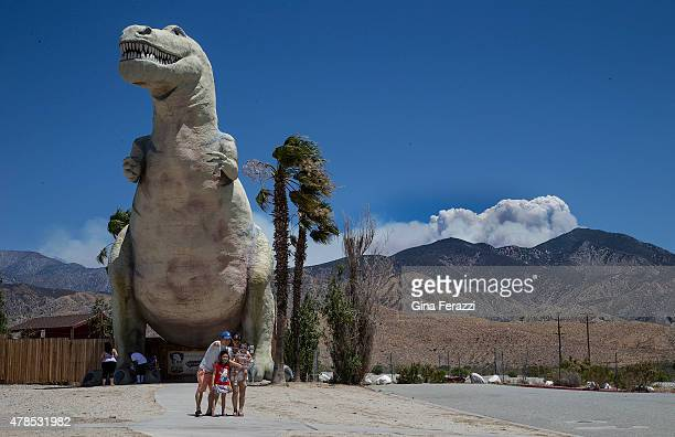 As the winds whip through the palm trees tourists take a selfie in front of a dinosaur exhibit while the a giant plume from the Lake Fire burns in...