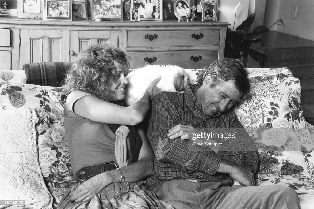As their cat climbs over them, American married couple, actress Jane Fonda and politician & activist Tom Hayden (1939 - 2016) share a laugh on their couch in their home, Santa Barbara, California, 1980s.