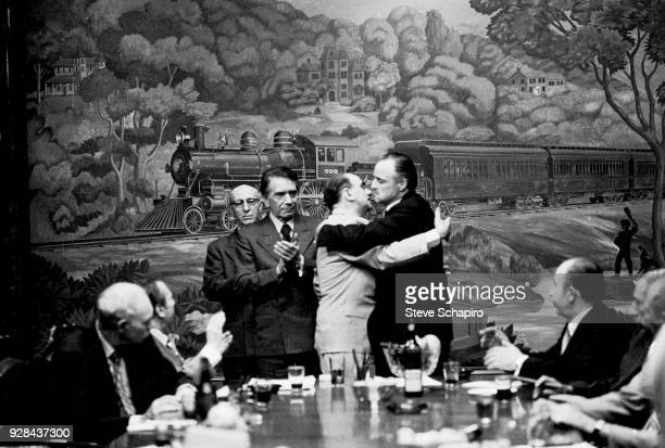 As their unidentified fellow actors watch American actors Richard Conte and Marlon Brando as they embrace on the set of their film 'The Godfather'...
