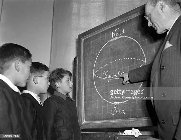 As three students watch an instructor teaches geography at the blackboard at an unidentified boys' school Venice Italy 1949